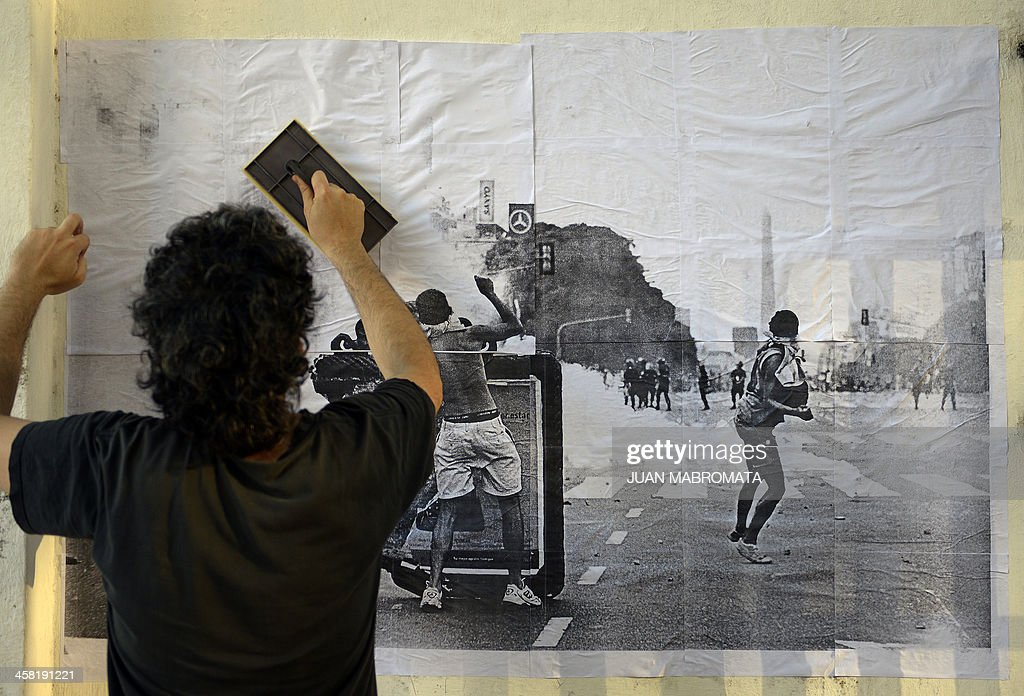 A man plasters a poster with an image taken during clashes back in 2001, on a wall, during a demonstration in downtown Buenos Aires to mark the 12th anniversary of the Argentine crisis, when Argentina declared the biggest debt default ever, on December 20, 2013.