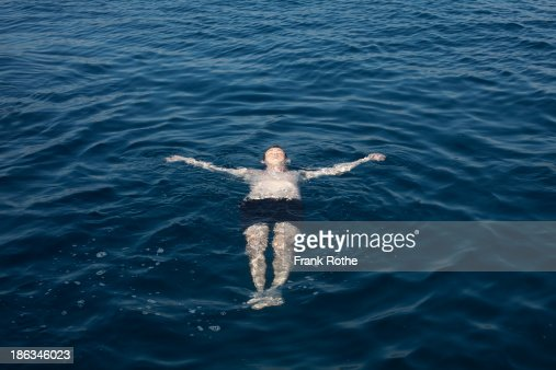 man playing a dead man in the water : Stock Photo