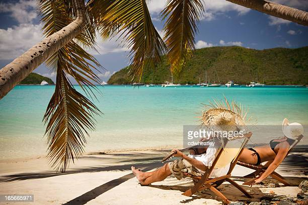 man playing a guitar at the beach, woman sunbathing
