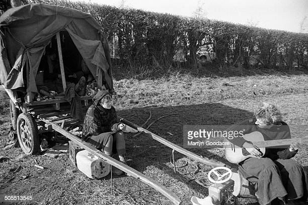 A man playing a guitar by a gipsy caravan at an encampment of New Age travellers near Hereford 1987
