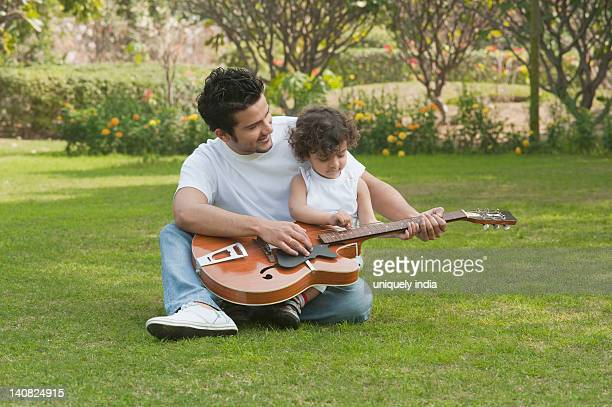 Man playing a guitar with his son sitting on lap