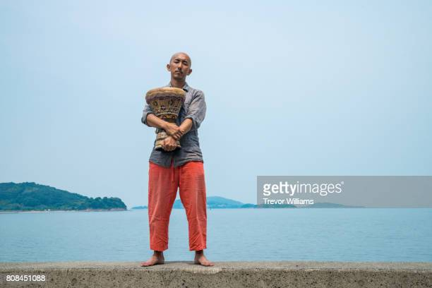 Man playing a percussion instrument near the sea