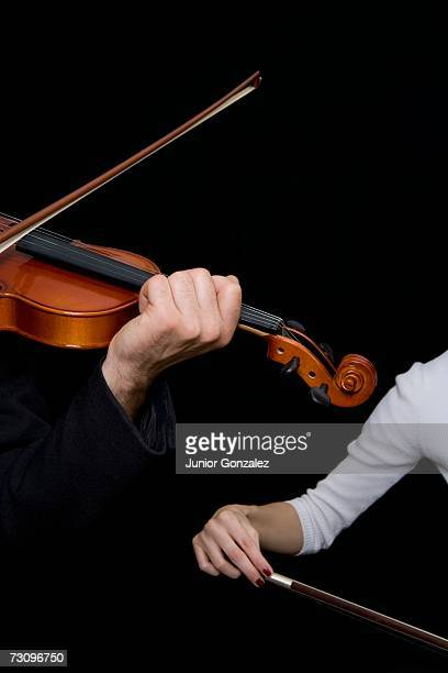 Man playing a violin and a woman playing a cello