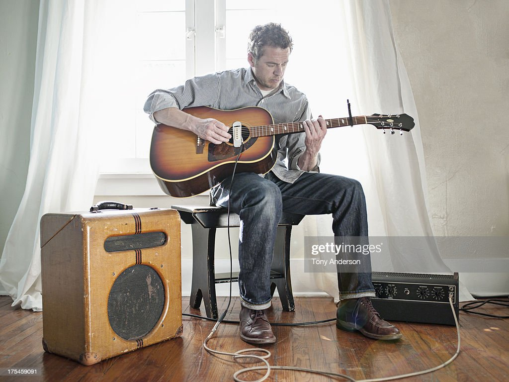 Man playing acoustic guitar with electric pick up : Stock Photo