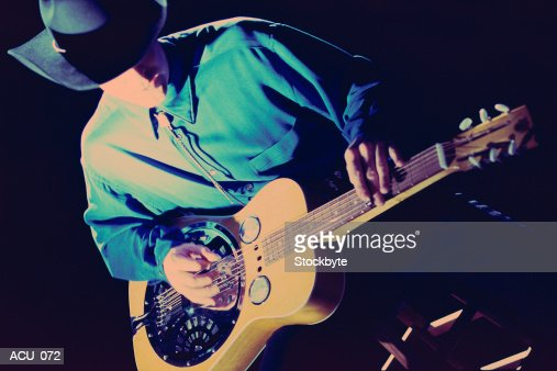 Man playing acoustic guitar with metal resonator : Stock Photo