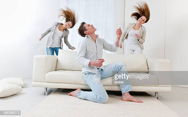 man playing air guitar and two dancing young women