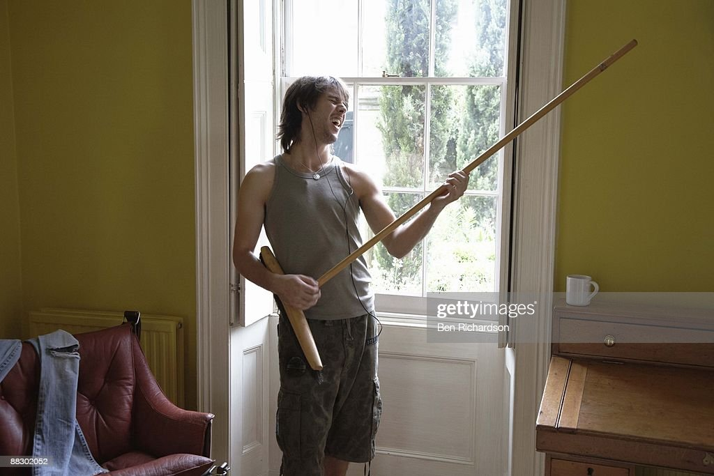 Man playing air guitar with broom