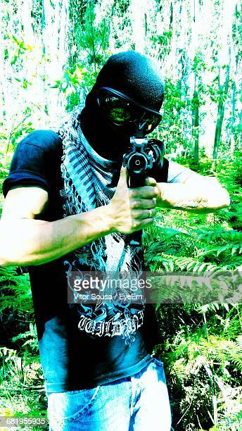 Man Playing Airsoft In Forest