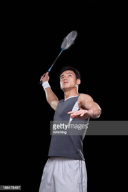 Man playing badminton, black background