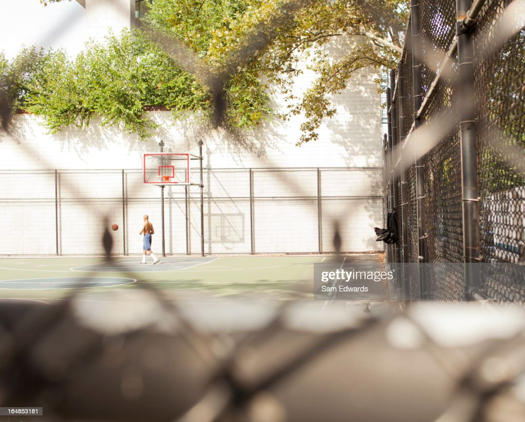Man playing basketball on urban court : Stock Photo