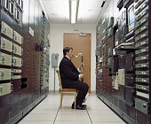 Man playing bass clarinet in server room, side view