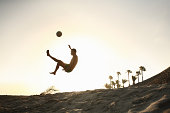 Man playing beach soccer at sunset