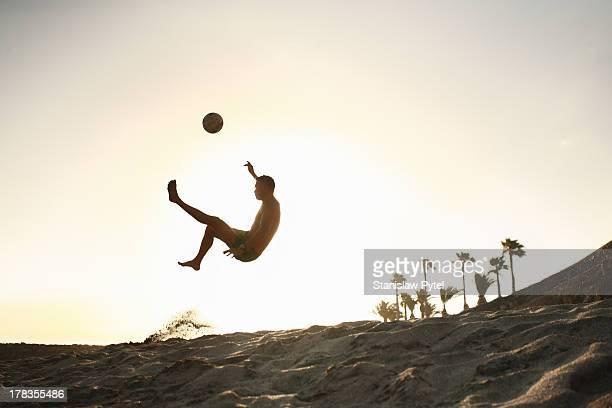 Man playing beach soccer at sunset
