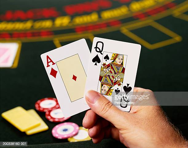 Man playing blackjack, close-up (focus on hand and cards)