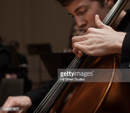 Man playing cello in orchestra