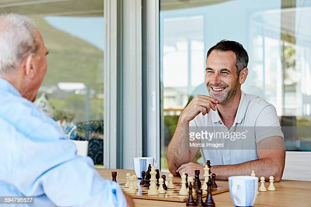 Man playing chess with father at patio