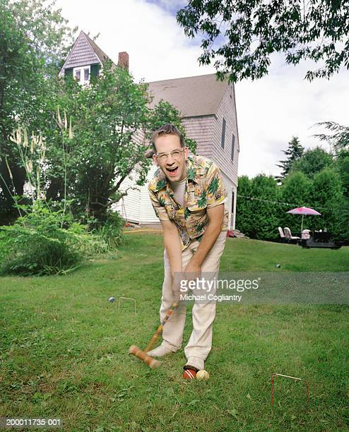 Man playing croquet on lawn