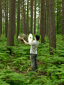 Man playing cymbals in forest, rear view