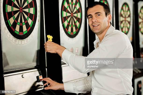 Man playing darts.