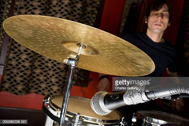 Man playing drums, eyes closed (focus on microphone in foreground)