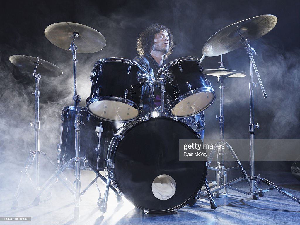 Man playing drums on stage surrounded by dry ice : Stock Photo