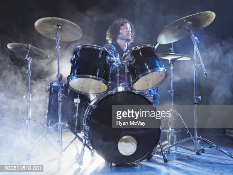 Man playing drums on stage surrounded by dry ice