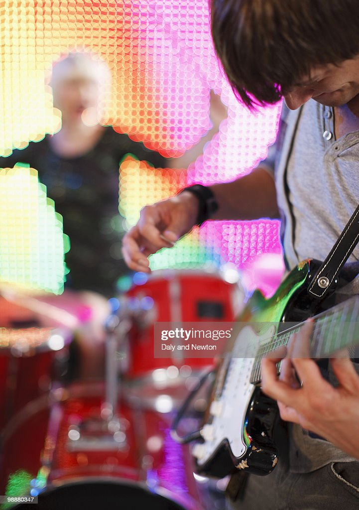 Man playing electric guitar, female drummer behind : Stock Photo