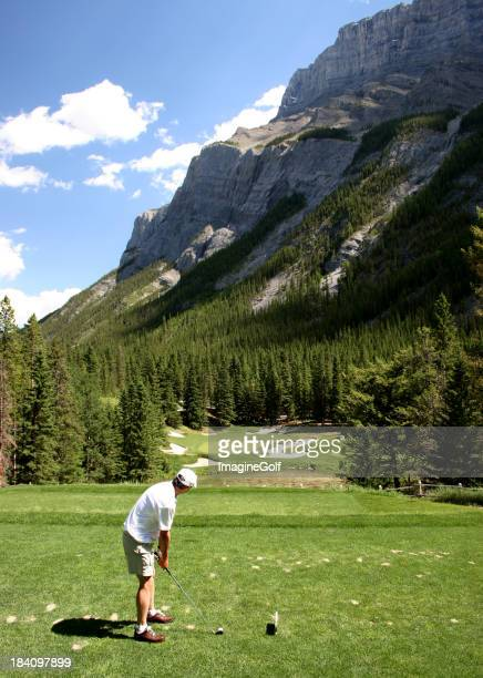 A Man Playing Golf in Front of a Rocky Cliff