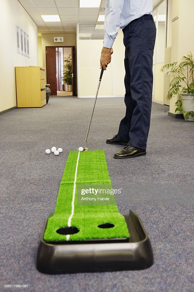 Man playing golf in office corridor, low angle view : Stock Photo