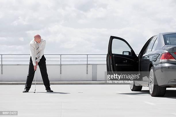 man playing golf near car