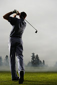 Man playing golf, rear view