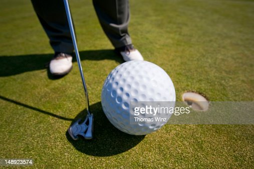 Man playing golf with oversized ball. : Foto de stock