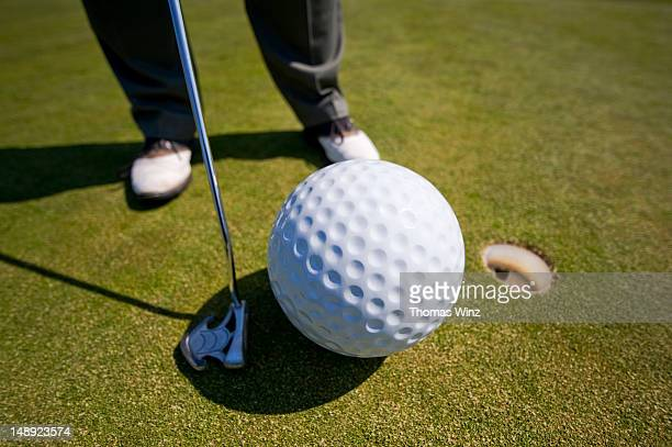 Man playing golf with oversized ball.