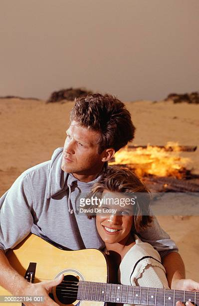 Man playing guitar and embracing woman on beach