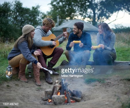 Man playing guitar around friends while glamping. : Stock Photo