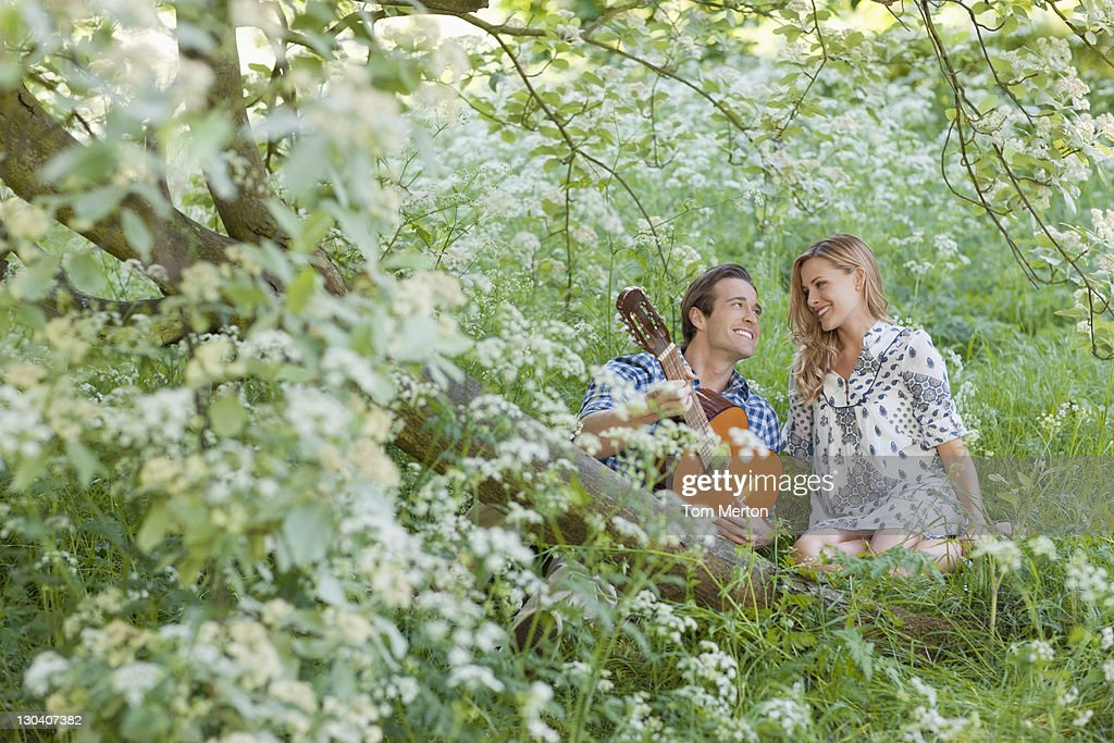 Man playing guitar for girlfriend in forest : Stock Photo