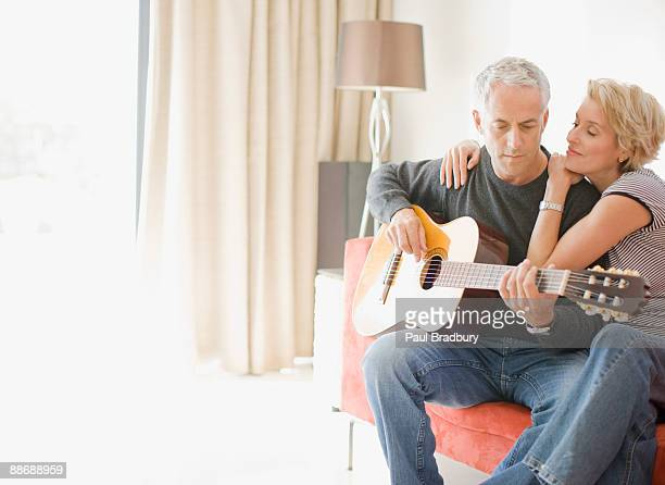 Man playing guitar for wife in living room