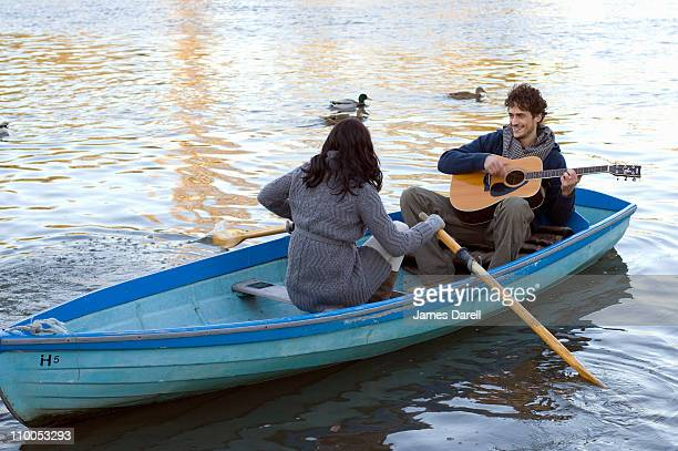 Man playing guitar in row boat