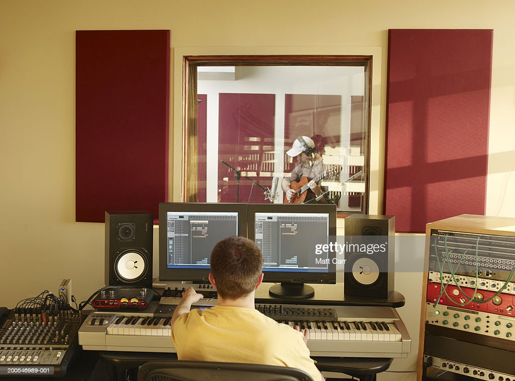 Man playing guitar in studio with engineer : Stock Photo