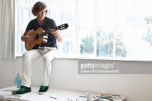 Man playing guitar in window