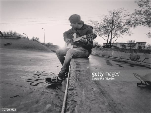 Man Playing Guitar On Roadside Against Clear Sky