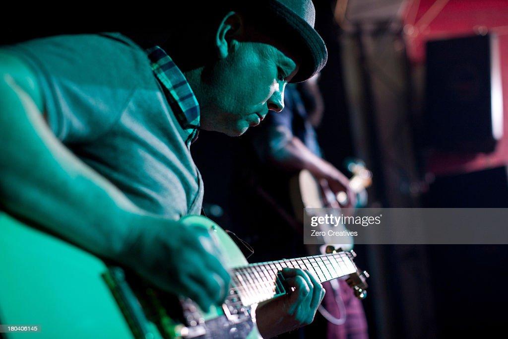 Man playing guitar on stage in nightclub