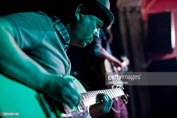 Man playing guitar on stage in nightclub