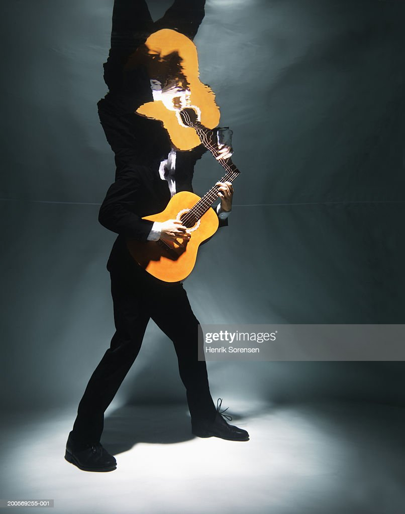 Man playing guitar underwater, low section : Stock Photo