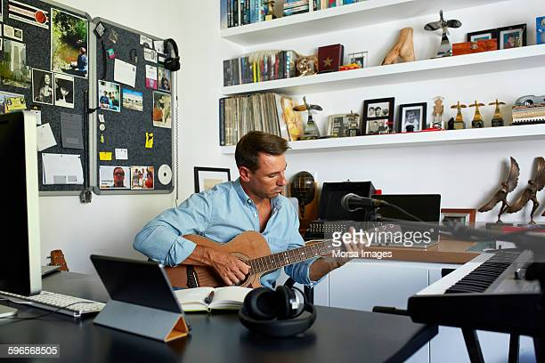 Man playing guitar while sitting at table