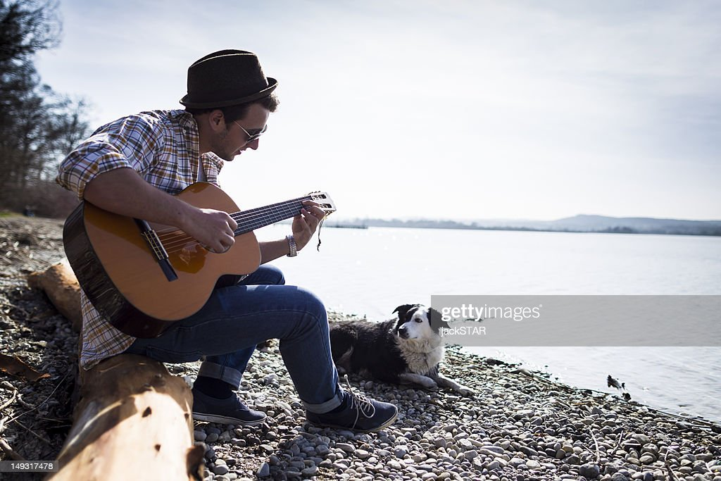 Man playing guitar with dog by creek