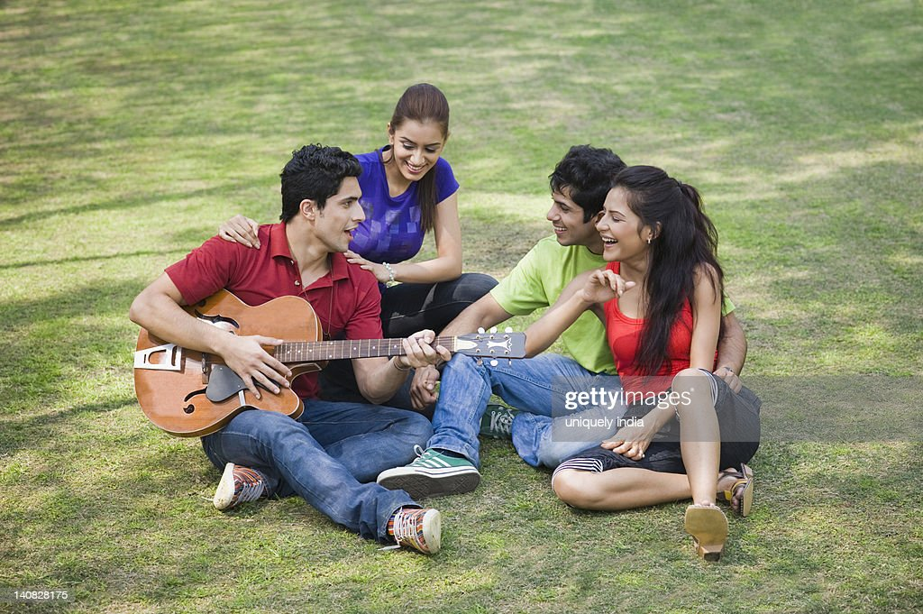 Man playing guitar with his friends sitting beside him : Stock Photo