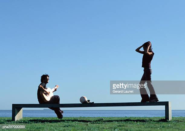 Man playing guitar, woman standing on bench near water.