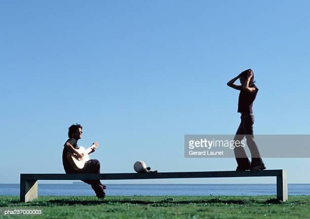 Man playing guitar, woman standing on bench near water.