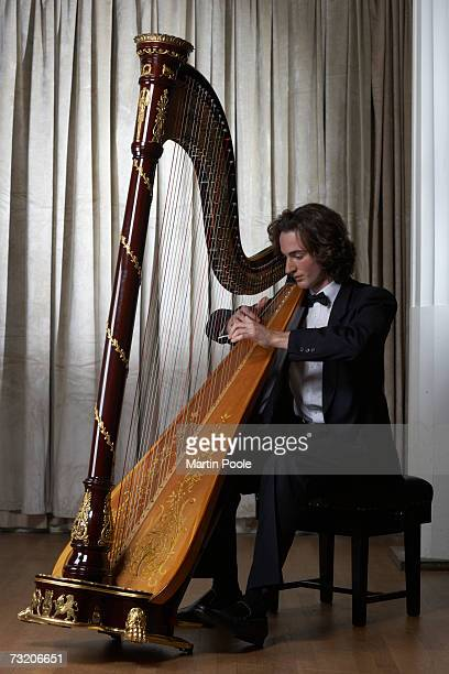 Man playing harp, full length